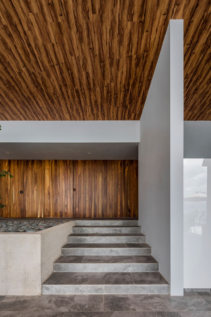 Stepping inside this modern house, there's an immediate warmth from the use of wood throughout the interior. A set of small stairs leads from the wood front door down into the open living area. #ModernHouse #WoodCeiling #WoodFrontDoor #InteriorSteps