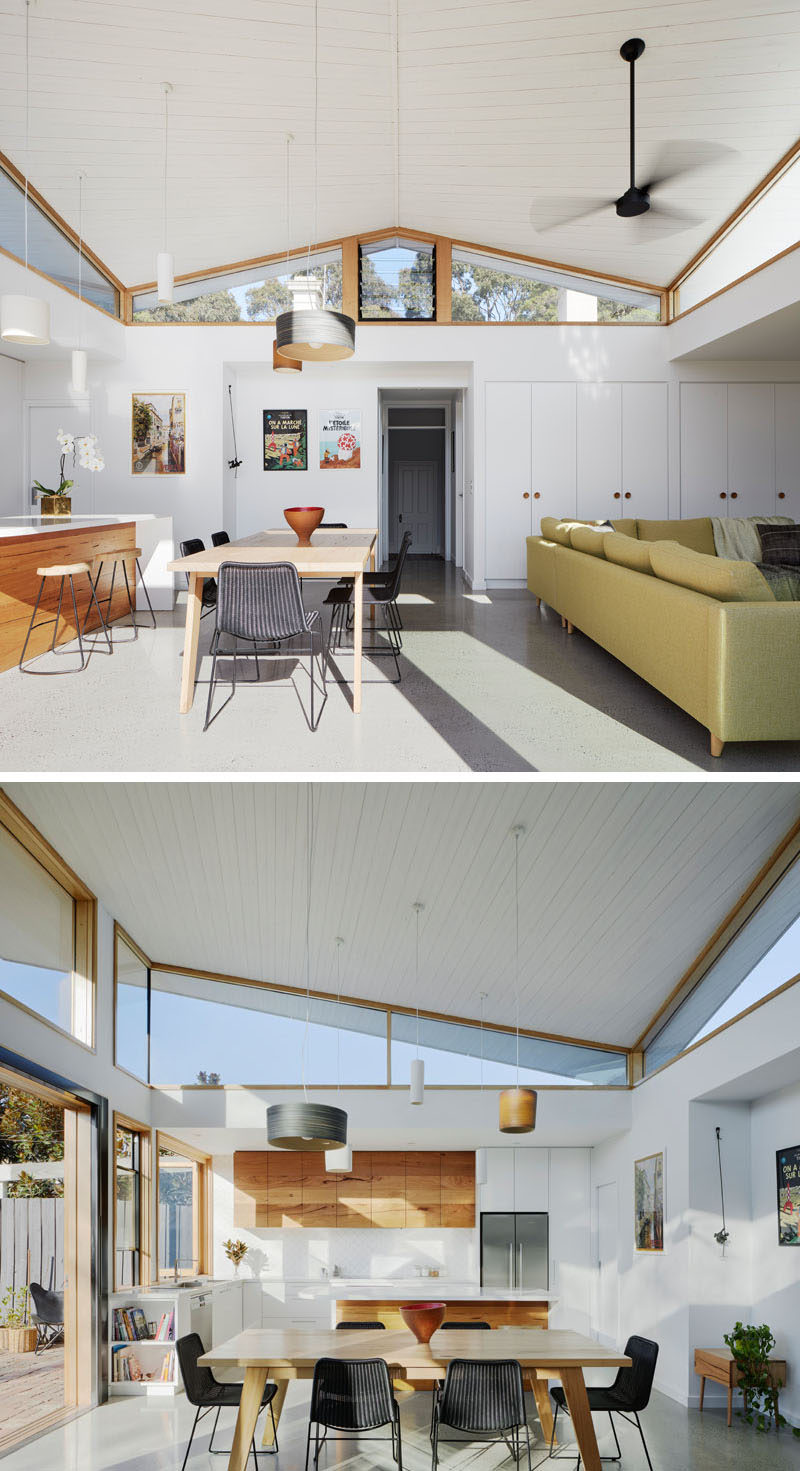Inside this modern house extension, there's a white timber ceiling that compliments the walls and built-in storage cabinets, and is used to create a sense of lightness to the space. #HouseExtension #Windows #Architecture