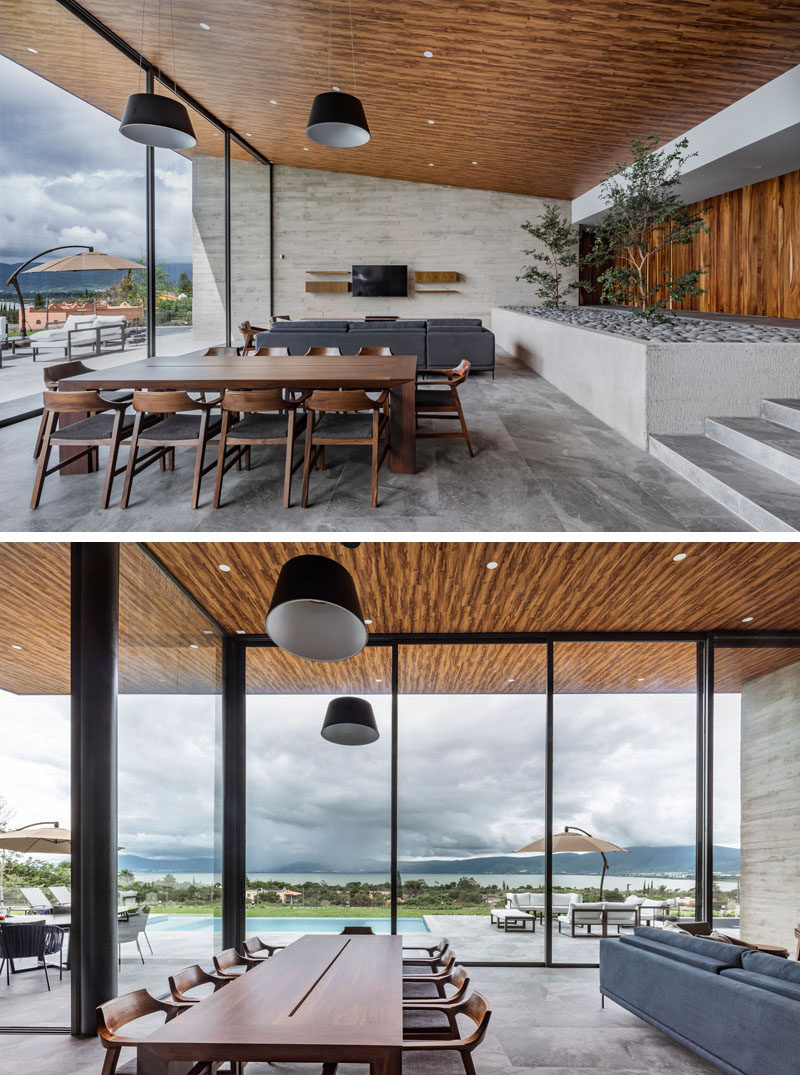 The living room and dining room in this modern house share the open space and look out to the backyard and views through large sliding glass walls. #SlidingGlassWalls #ModernDiningRoom #WoodCeiling