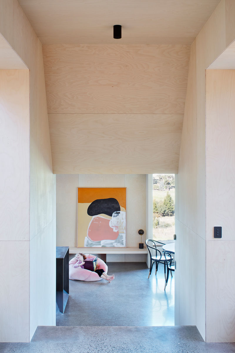 Birch-faced plywood is featured throughout this modern house to create a sense of warmth and to reinforces the monolithic form of the interior's angled ceilings. #ModernHouse #PlywoodInterior