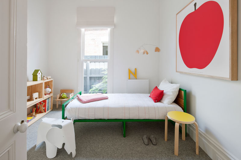 A colorful green bed and bright artwork helps to define this modern child's bedroom. #KidsRoom #KidsBedroom #InteriorDesign