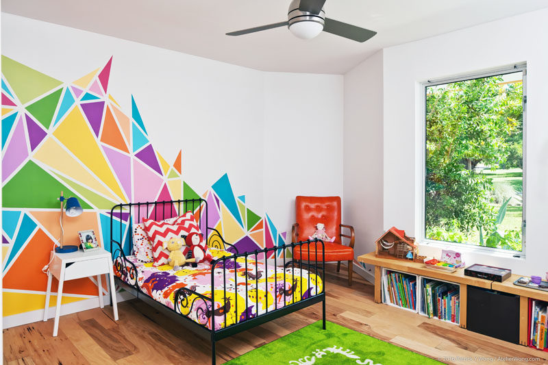 In this modern bedroom, a large, colorful and graphic mural brightens up the white walls, while a window gives views of the gardens. #BedroomDesign #KidsBedroom #ModernBedroom #GraphicMural