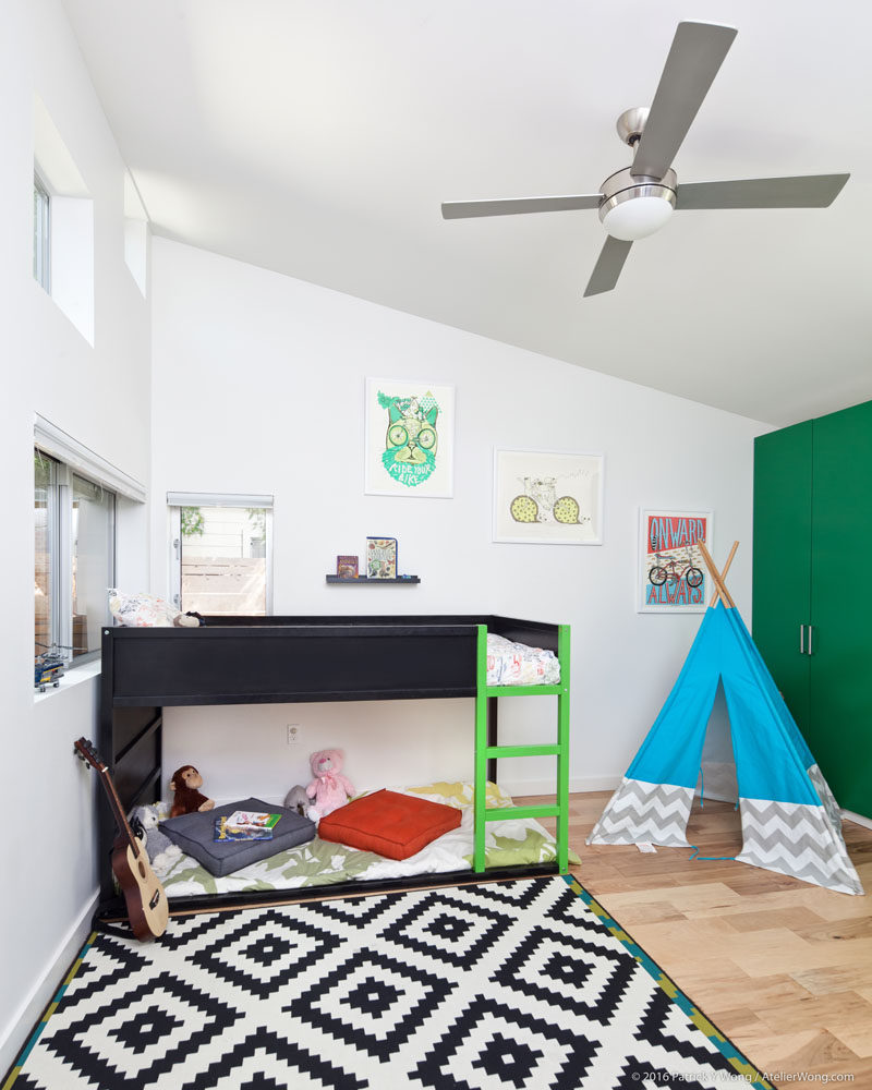 In this kid's bedroom, a high sloped ceiling creates a sense of openness and allows for a raised bed to be included. #KidsBedroom #BedroomDesign