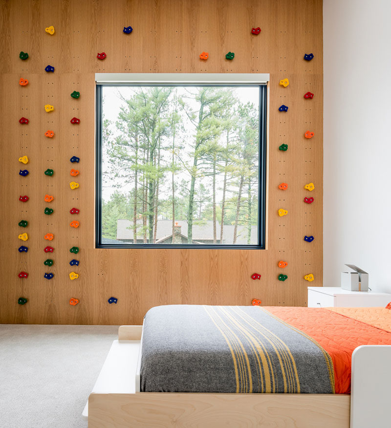 In this modern kids bedroom, a rock climbing wall surrounds the window and small sets of holes in the wood wall allow the 'rocks' to be moved to create a new climbing challenge when needed. #RockClimbingWall #KidsBedroom #BedroomDesign
