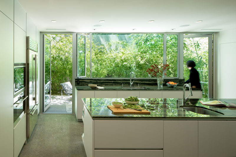 This minimalist white kitchen with dark countertops has views of the garden, and two floor-to-ceiling glass doors can be opened to a small patio area. #MinimalistKitchen #WhiteCabinets #ModernKitchen