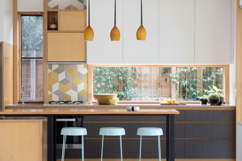 In this modern kitchen, windows have been used as a backsplash, plus they allow natural light and a view of the garden, while a small section of colorful tiles adds a playful touch. #ModernKitchen #Windows #KitchenWindow #KitchenDesign