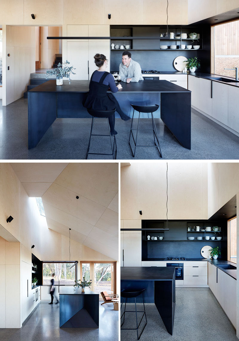 The modern plywood kitchen has been designed as a communal zone with plenty of space. A large black island with seating matches the black shelving, backsplash and countertop, creating a bold and contemporary look. #ModernKitchen #Wood #BlackIsland #KitchenDesign