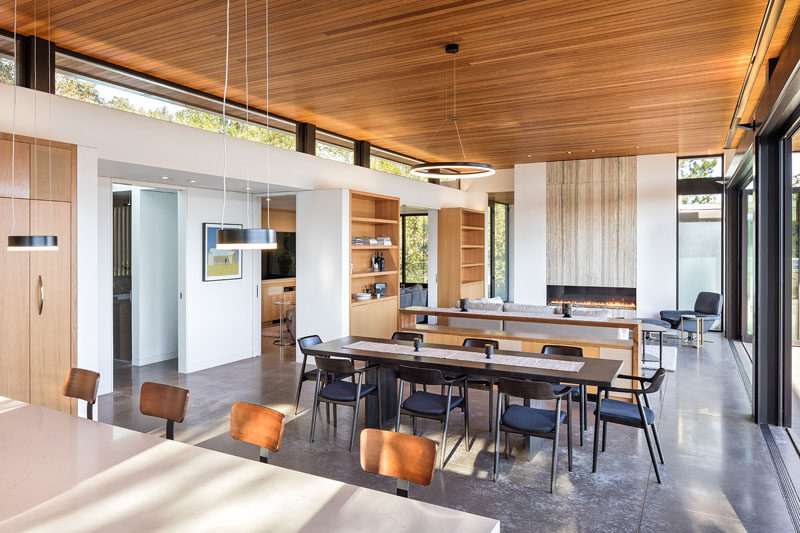 Inside this modern house with an open plan interior, clerestory windows provide a separation between the walls and the wood ceiling, while a large fireplace has a stone accent above it. #Windows #Fireplace #ModernInterior