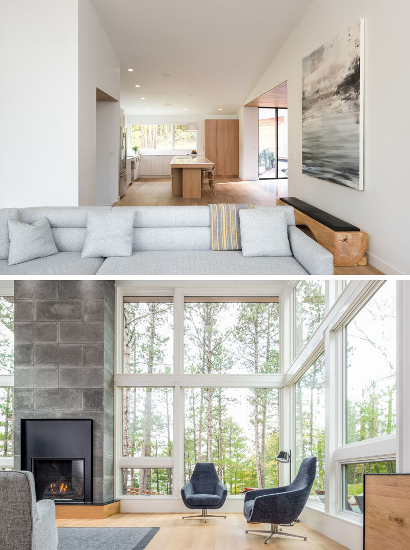 Large windows wrap around this modern living room and show off the tree views, while a fireplace creates a focal point in the room. #ModernLivingRoom #Windows #Fireplace
