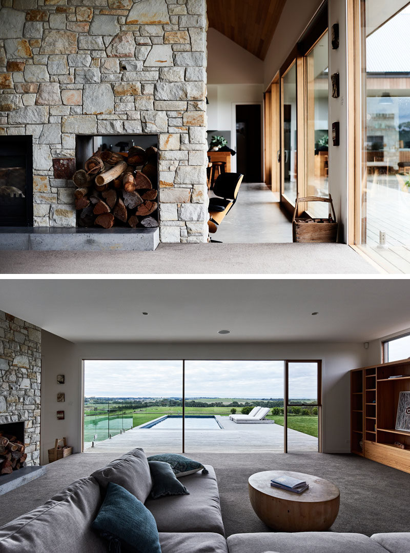 Stepping up from the main social room in this modern ranch-inspired house, is a living room with a built-in shelving unit to house the television. Large windows provide a view of the landscape and pool outside. #StoneFireplace #Windows #LivingRoom