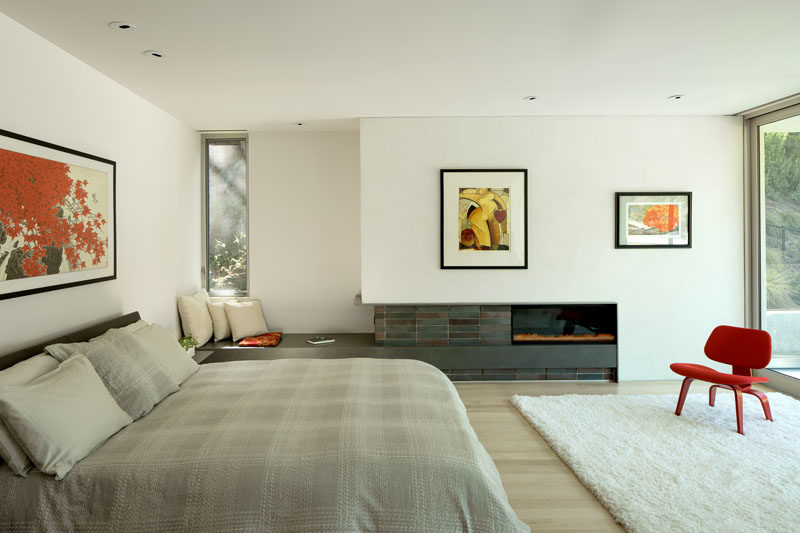 This modern master bedroom looks out over the pool and backyard, while inside, there's a fireplace and a built-in bench for relaxing. #MasterBedroom #Fireplace #SeatingNook