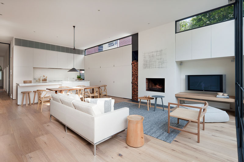 This modern open plan interior has a fireplace and wood storage that sits flush with the minimalist white cabinets in the kitchen. #WhiteKitchenCabinets #ModernLivingRoom #ModernFireplace #WoodStorage