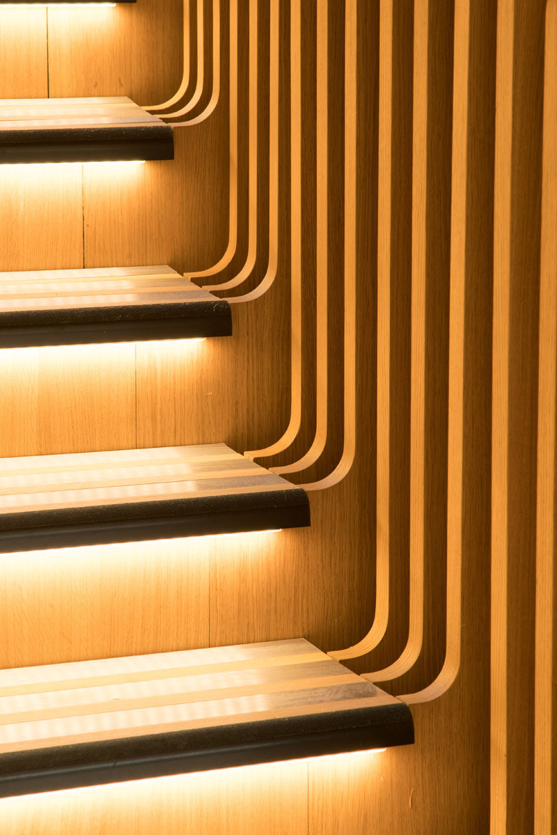 Each of the stair treads in this sculptural staircase have hidden lighting beneath them. #StairTreads #WoodStairs #StairDesign #HiddenLighting