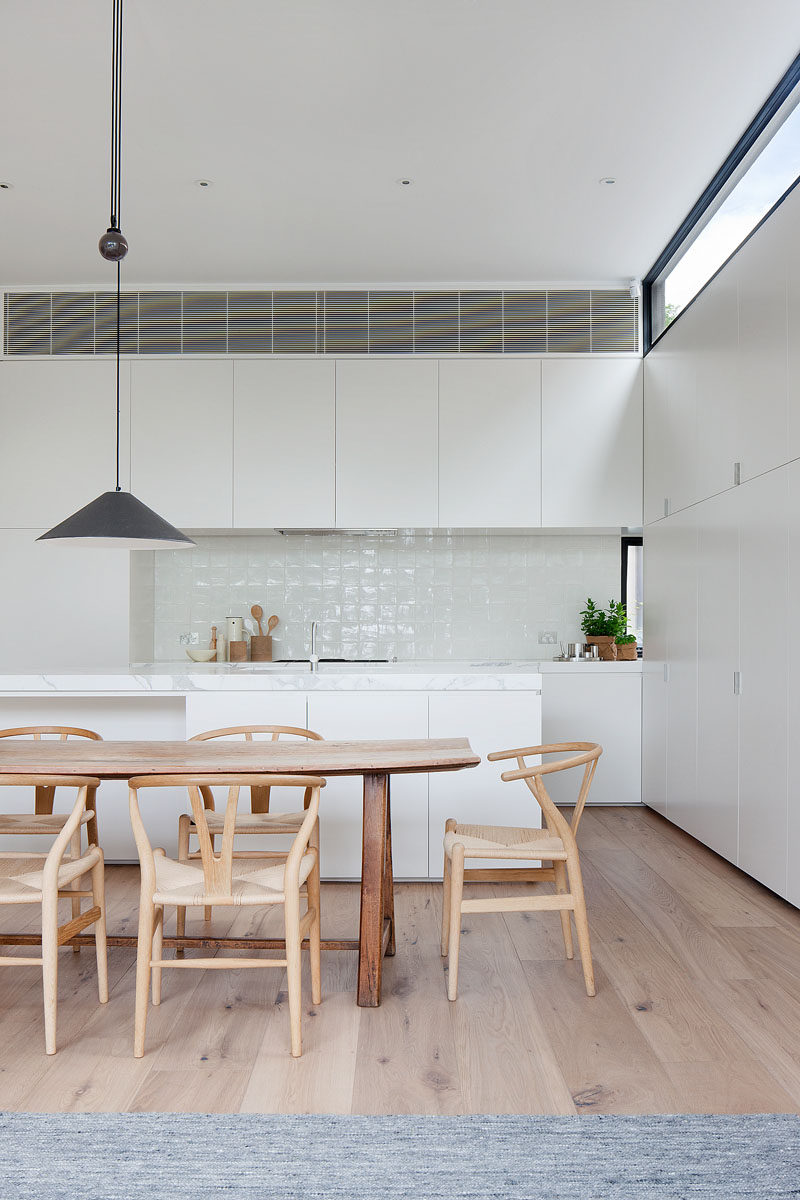 The light wood dining table and chairs, combined with the flooring, add a sense of warmth to the mostly white modern interior. #DiningRoom #WhiteKitchen #WoodFloors #InteriorDesign
