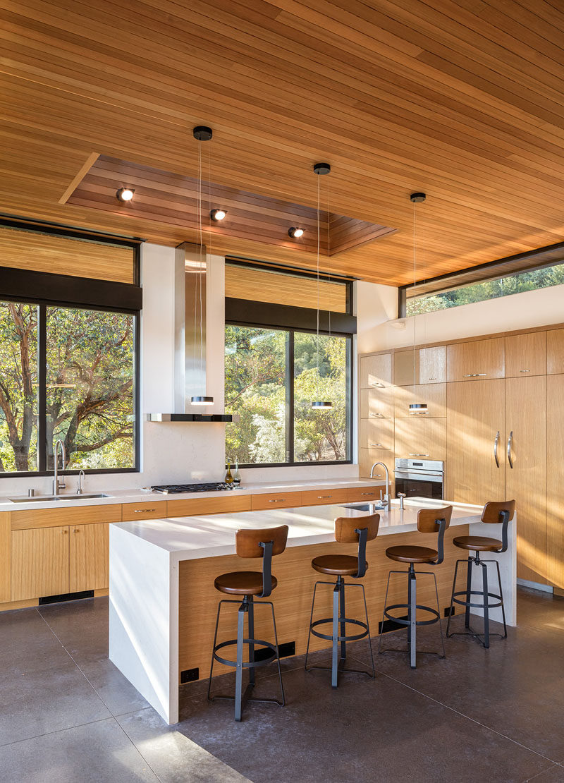 In this modern kitchen, light wood cabinets, white countertops, large windows and a skylight all help to keep the kitchen bright and airy. #ModernKitchen #LightWoodCabinets #WoodCeiling