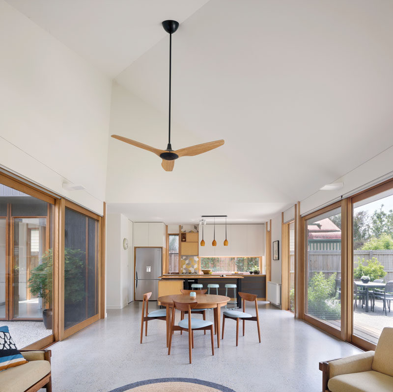 In this dining area, it's easy to see how open the house is, with sliding doors on either side that open to the courtyard and the backyard. #ModernHouse #OpenPlanLiving #HighCeilings
