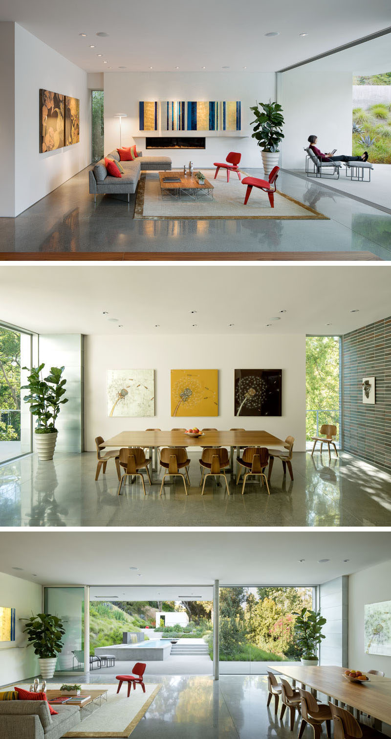 Inside this modern house, the main living areas of the home are open plan, with the living room and the dining room sharing the space, while a large sliding glass door opens to the backyard. #ModernLivingRoom #ModernDiningRoom #OpenPlan