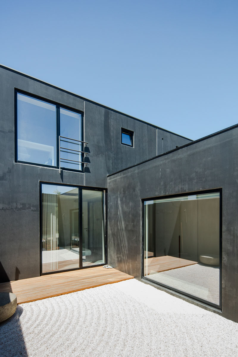 This small and private courtyard off the master bedroom has a small wood patio area and the rest is covered in rippled sand. #ModernHouseDesign #Courtyard #Windows
