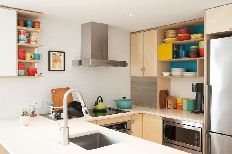 This kitchen has open shelving that allows the collections of colorful vintage cookware to be on display. #OpenShelving #PlywoodKitchen #KitchenDesign