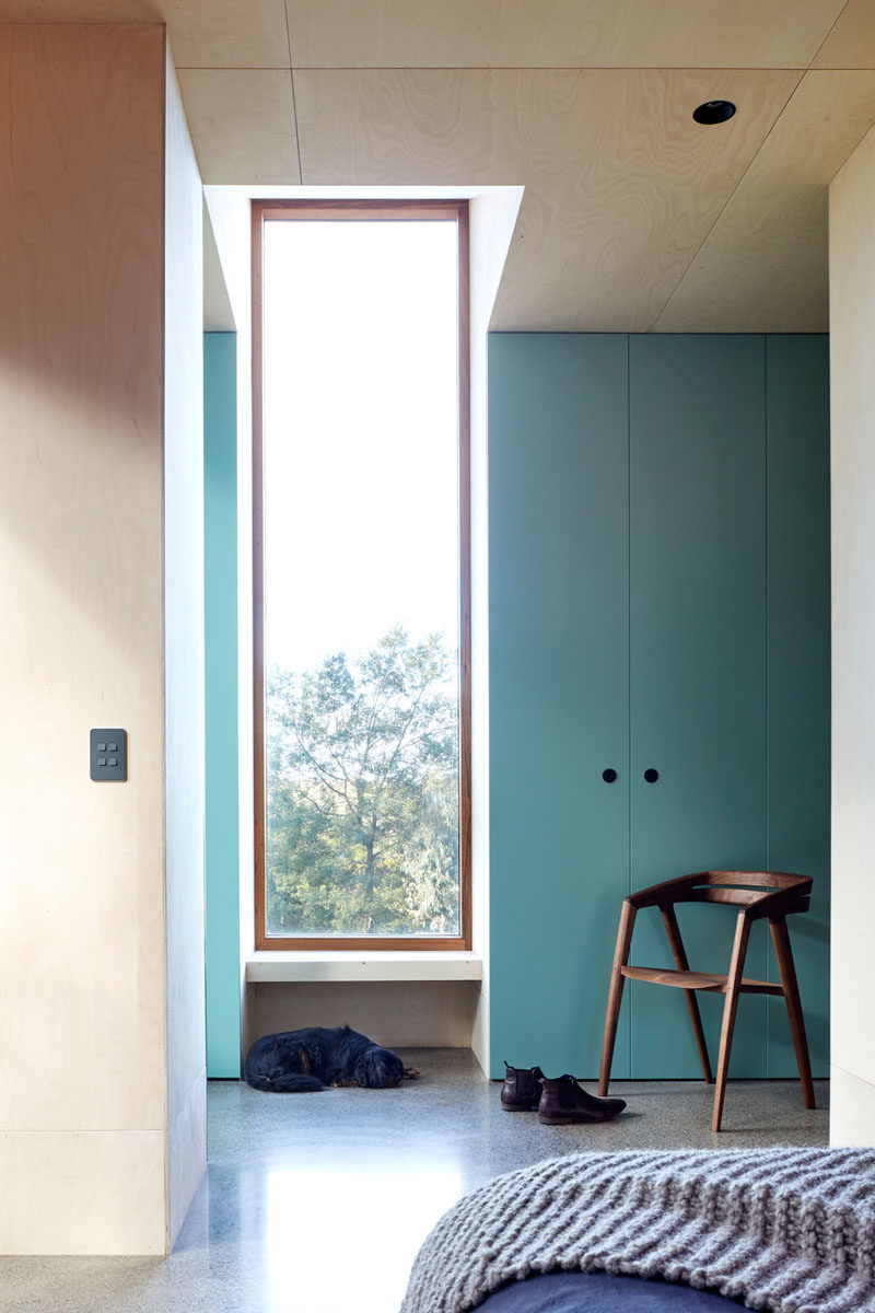 A pop of color has been added to this modern bedroom by the use of light blue, floor to ceiling cabinets. #Blue #Storage #Windows #Bedroom