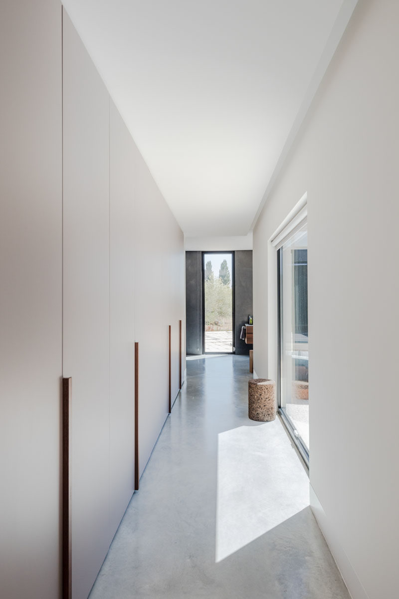 A long row of minimalist cabinets that act as a walk-through closet, connecting the master bedroom with the bathroom. #Closets #Wardrobe #InteriorDesign