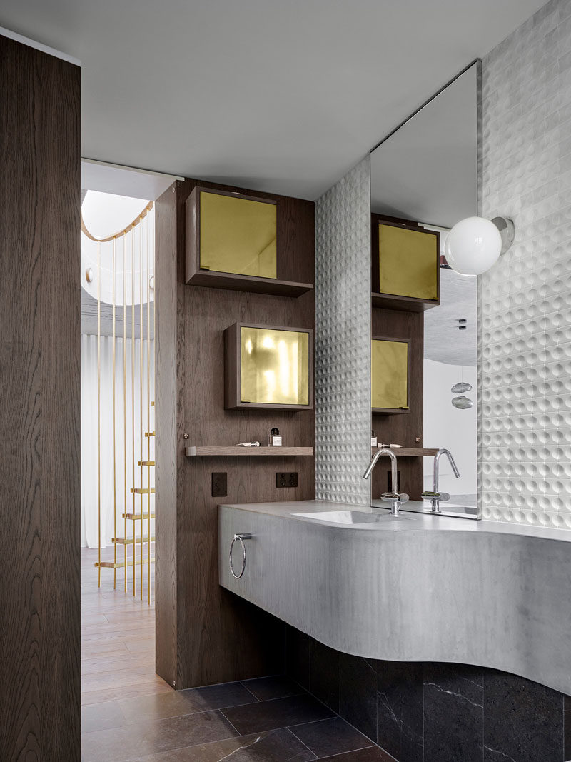 A curved concrete basin and bench creates an interesting sculptural detail in this modern powder room. #ConcreteVanity #BathroomDesign