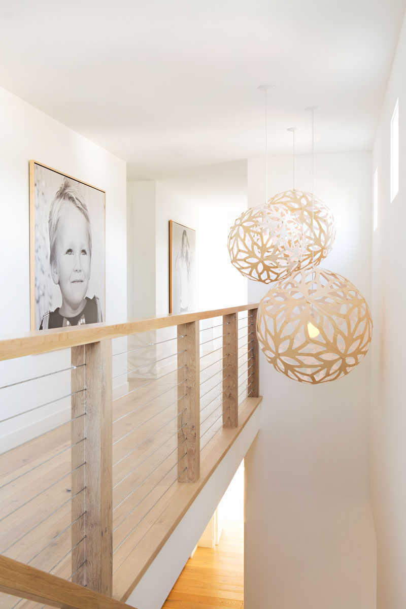 Simple decorative pendant lights hang above the stairs, while a simple wood and wire cable handrail continues with the farmhouse look. #PendantLights #Handrail #InteriorDesign