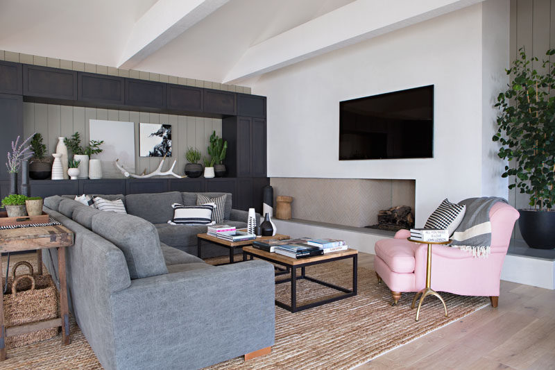 In this contemporary living room, dark cabinetry along one wall creates plenty of storage as well as a place to display favorite items, while a fireplace, comfortable couch and rug, all add a sense of warmth to the room. #LivingRoom #Fireplace #GreyCabinets