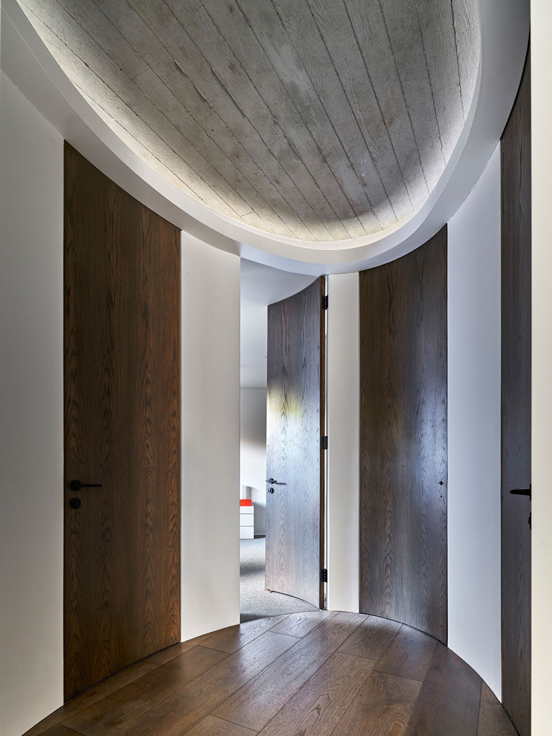 This modern oval-shaped hallway has custom, full-height, curved doors that lead to the bedrooms and bathrooms. #CurvedDoors #Hallway #InteriorDesign