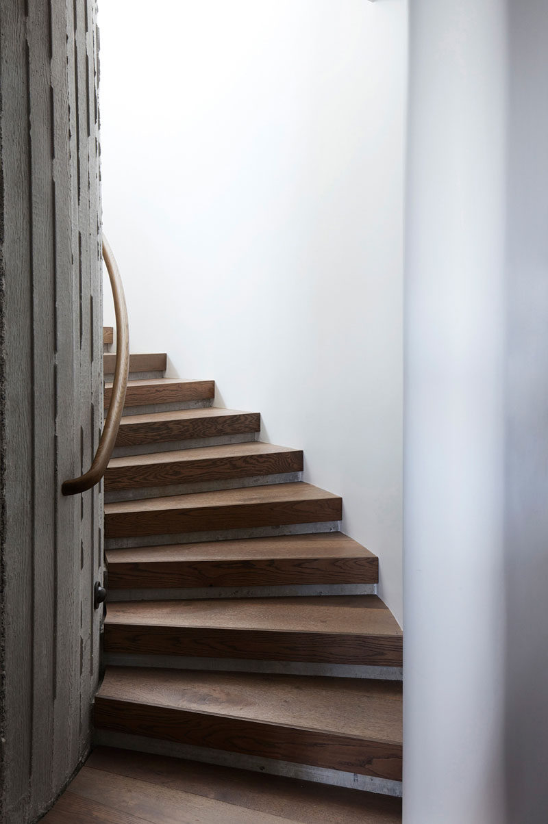 This modern elliptical shaped stairwell has white and concrete walls, and stair treads made from oak. #WoodStairs #CurvedStairs