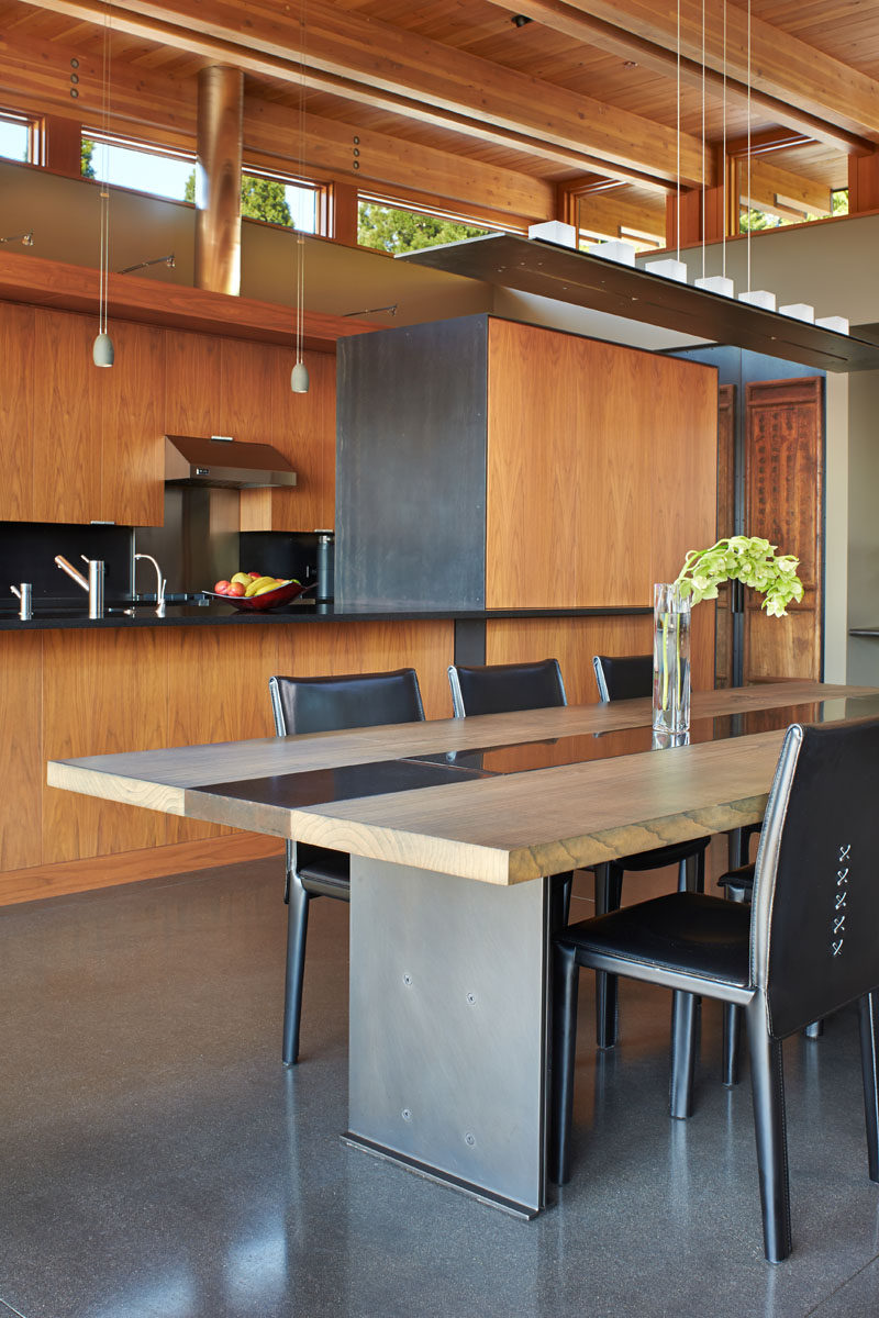 In this contemporary dining room, a custom-designed glass and metal chandelier sits above a custom dining table that's made from wood, steel and concrete. #DiningRoom #DiningTable