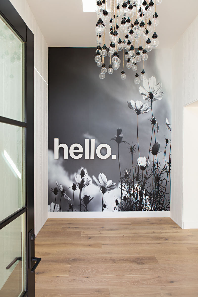 In this modern home entryway, you are greeted by an artistic bare-bulb light installation and a simple 'hello' mural covers the wall. #Entryway #Mural #Lighting