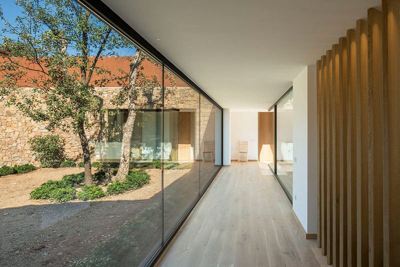 A wall of floor-to-ceiling windows with a view of a courtyard line this hallway that leads to the various areas of the home. #Hallway #Windows