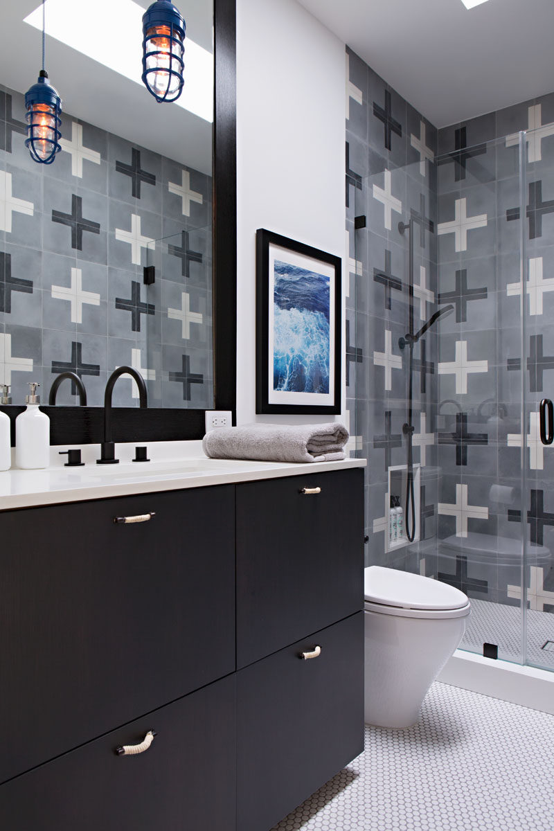 In this modern kids bathroom, fun tiles with a plus pattern have been used in the shower, while a built-in shower shelf is at the perfect height for little kids. The black vanity, faucet and mirror frame compliment the black in the tiles. #KidsBathroom #ModernBathroom