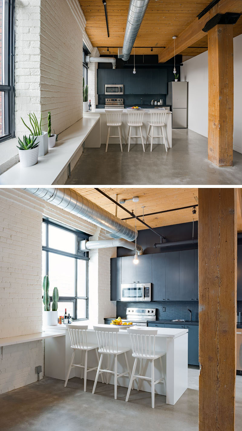 In this kitchen in a modern loft, there's a dark accent wall that draws your eye, while along the windows, a 'work bench' was added to create a space to work, display art or use when hosting a party. #KitchenDesign #Loft #InteriorDesign
