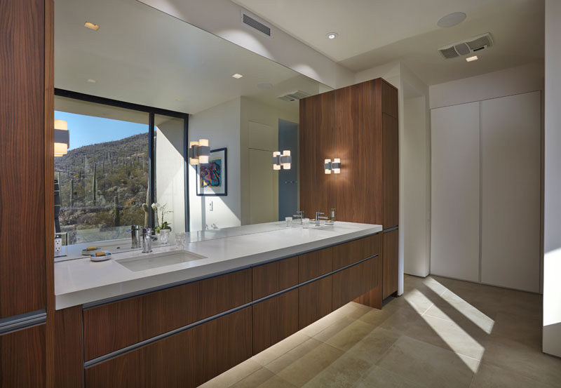 In this modern bathroom there's a large double sink, wood vanity with plenty of storage, and the large mirror reflects the views from outside. #ModernBathroom #LargeVanity #WoodVanity