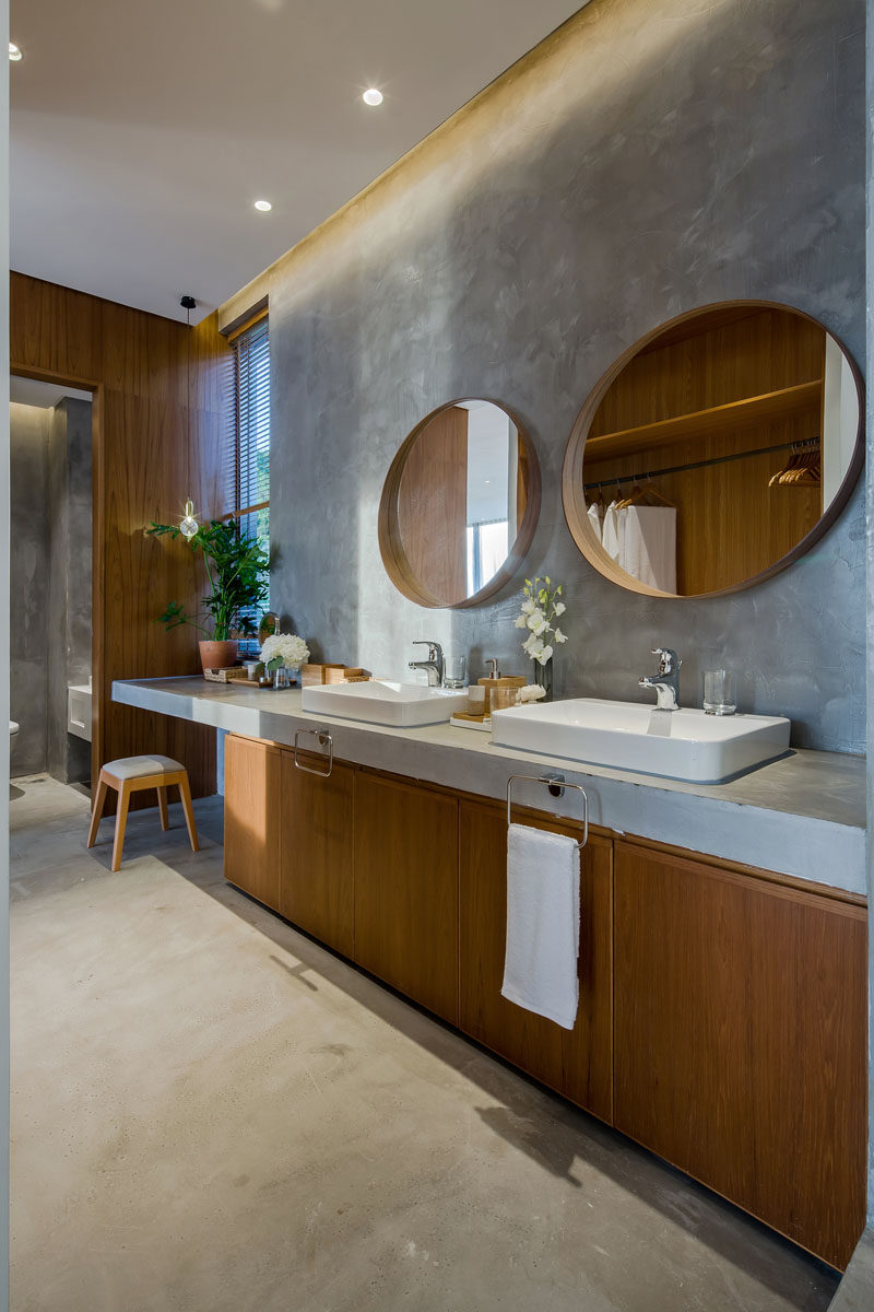 This modern bathroom has a large wood vanity with a concrete countertop that matches the floor. A round wood-framed mirror hangs above each sink, while the vanity extends to create additional counter space with an open space for a stool. #ModernBathroom #WoodAndConcreteBathroom #RoundMirrors #ConcreteCountertop