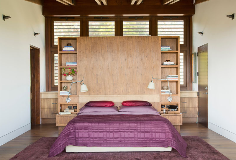 In this modern bedroom, a wood headboard has built-in bedside tables and open shelving for displaying personal items. #BedroomDesign #ModernBedroom #WoodHeadboard