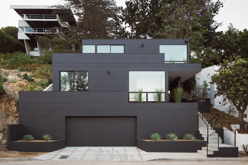 Aaron Neubert Architects have designed the Tilt-Shift House, a modern house that has a striking, bold black exterior and sits on a steep slope in the hills of Los Angeles. #BlackHouse #ModernHouse #Architecture
