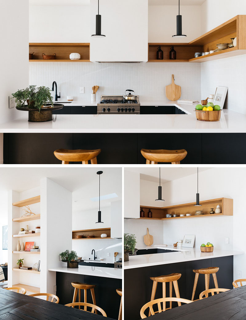 The upper half of this modern kitchen is kept bright with the use of white walls and wood shelving. The lower half with the cabinetry is matte black, creating a strong contrast to the rest of the kitchen. #ModernKitchen #BlackAndWhite #KitchenDesign