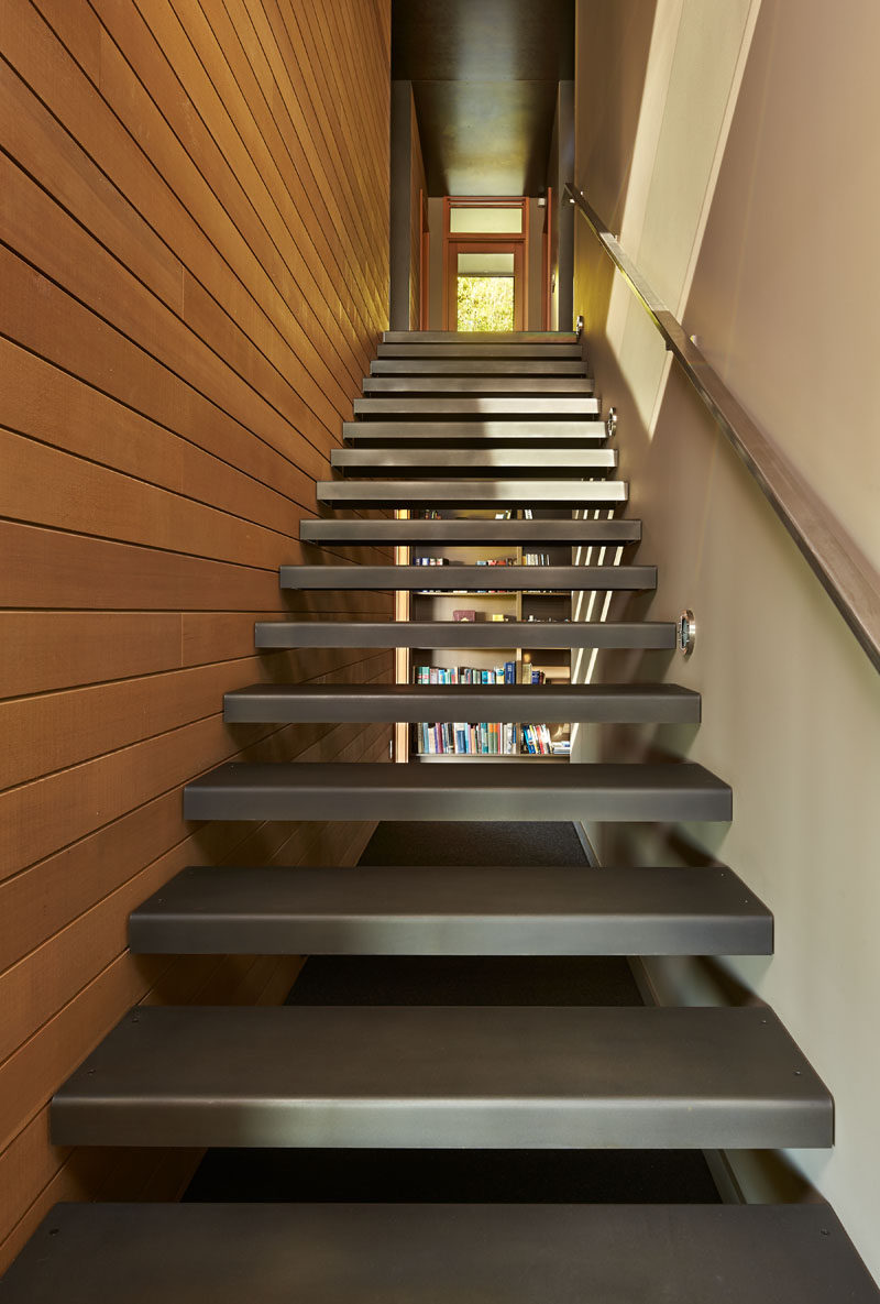 A blackened steel staircase that leads down to the lower floor of this modern house. #SteelStaircase #Steel #Stairs