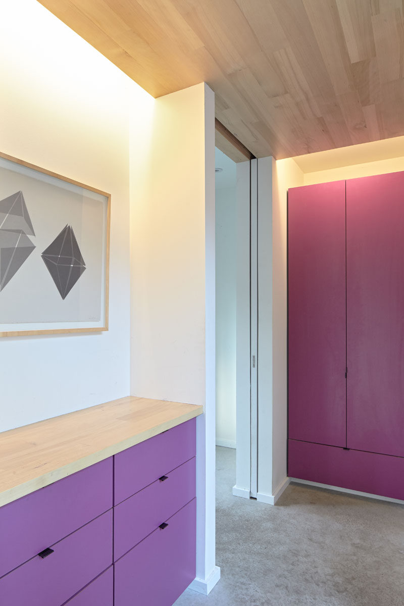 Stepping inside this modern house, you are hit with a burst of color with bright pink and purple cabinetry. Through a pocket door is the laundry, and hidden lighting in the ceiling creates ambient lighting in the entry. #BrightCabinets #InteriorDesign