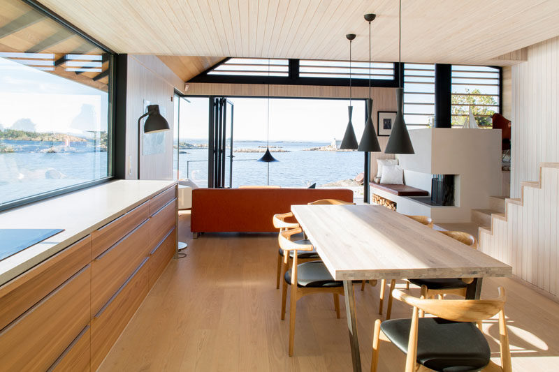 In this modern kitchen, a large picture window floods the space with natural light, while the dining table is positioned in the center of the space. #KitchenDesign #Windows