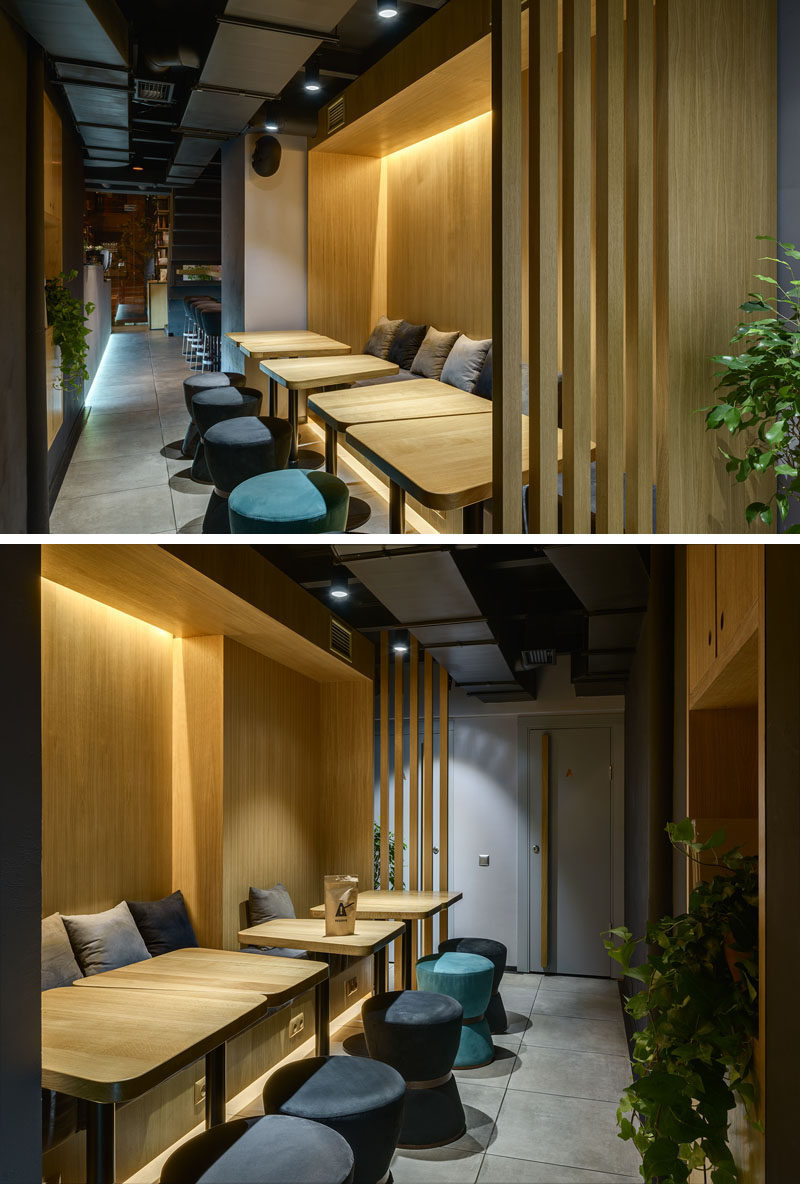This modern coffee shop seating area is surrounded by wood with banquette seating, wood tables, upholstered stools and hidden lighting. #ModernCoffeeShop #CafeSeating #InteriorDesign