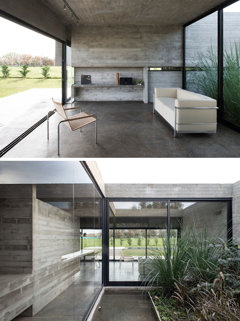 Large sliding glass walls open up the interior spaces of this modern concrete house to the backyard, and behind the living room is an inner patio with plants and another smaller water feature. #ConcreteHouse #LivingRoom #InnerPatio