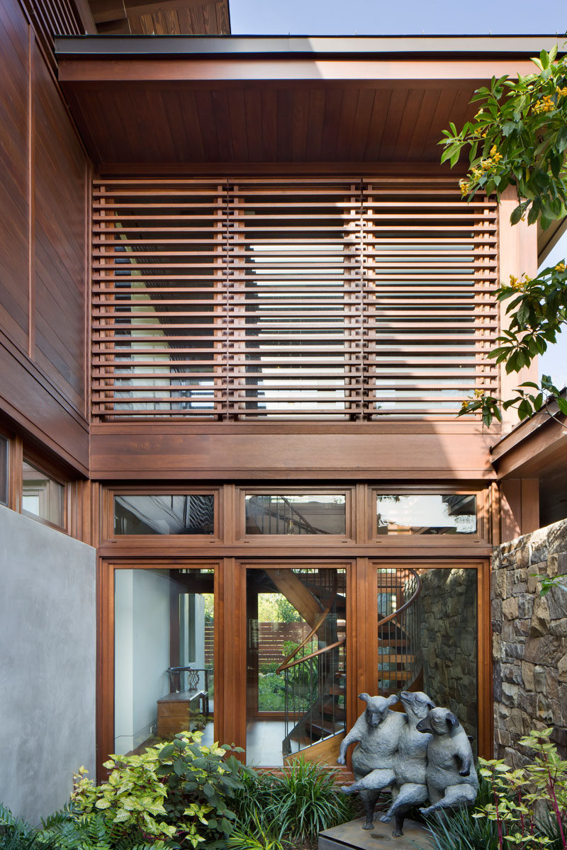 This modern wood house has a small garden with a cheerful sculpture. #Garden #Architecture