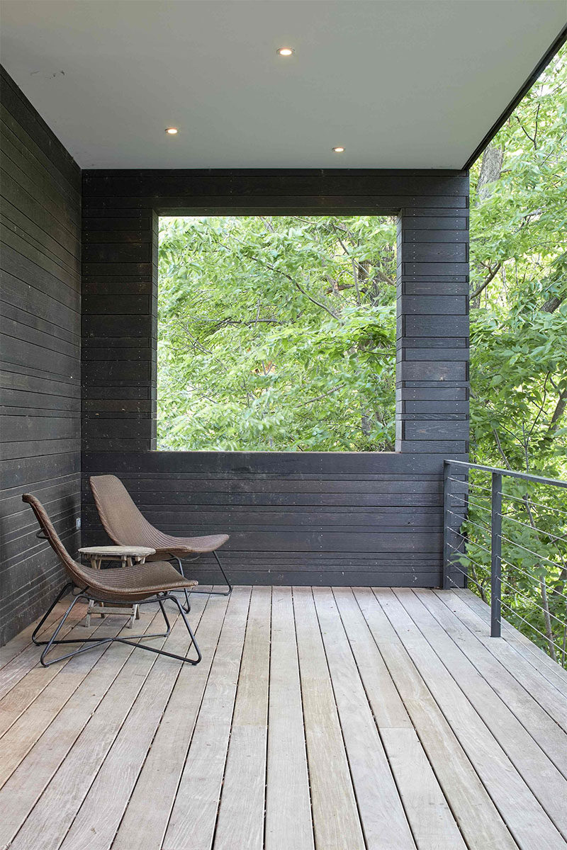 This modern, covered wood porch, sits at the front of a house and overlooks the street below. #CoveredPorch #ModernPorch