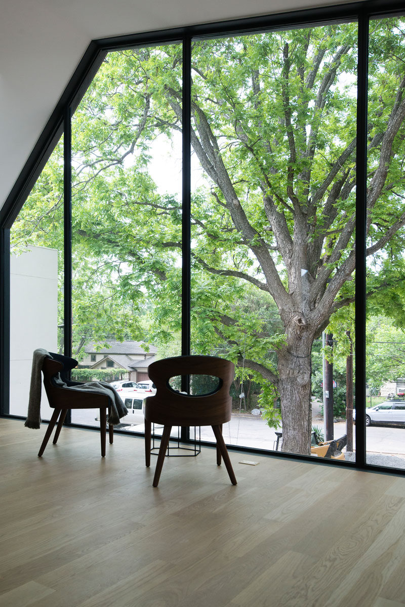 Large windows in this modern bedroom provide views of the trees and the street below. #LargeWindows #WindowDesign #Windows