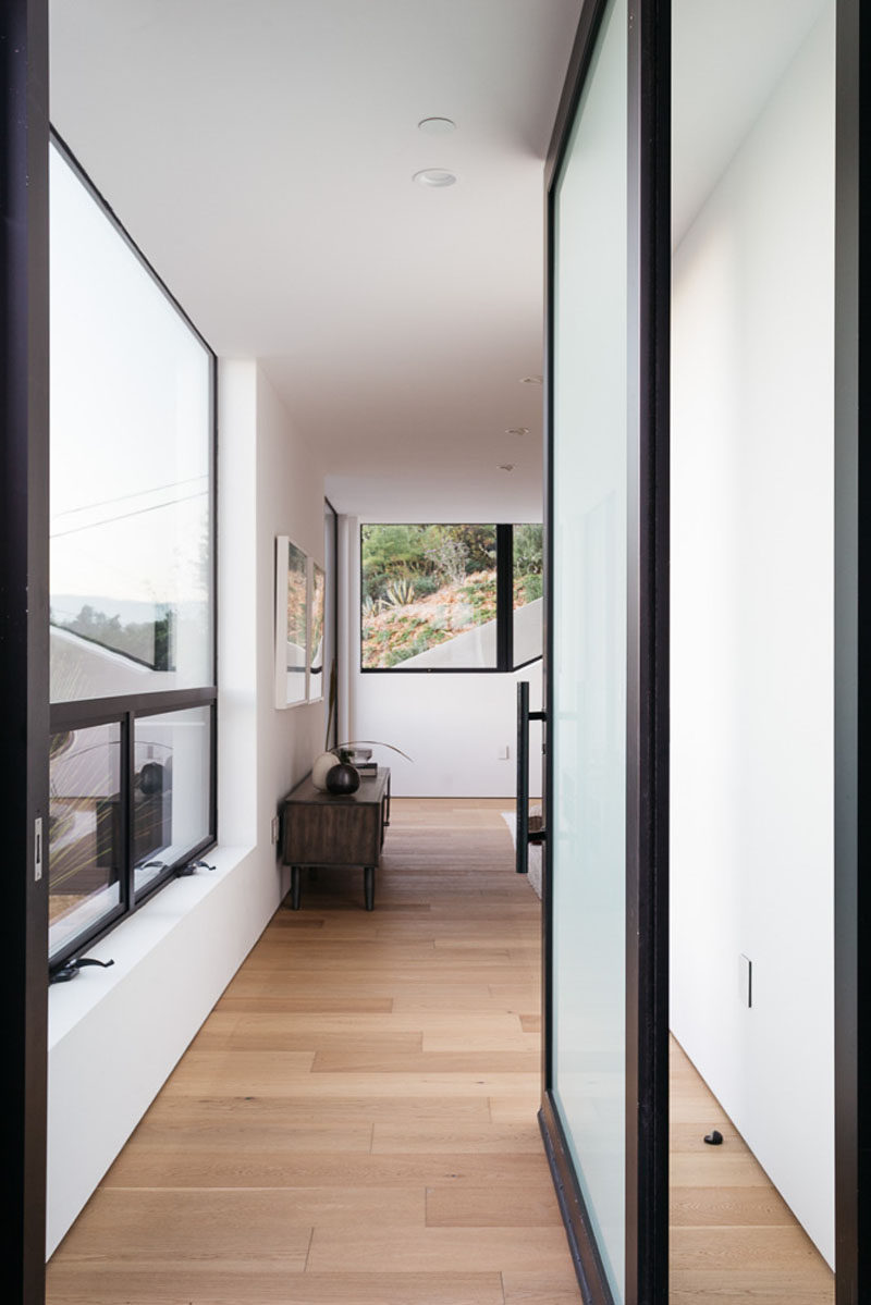 A semi-transparent front door and large windows allow natural light to fill the interior of this modern house. #FrontDoor #Windows #WoodFlooring