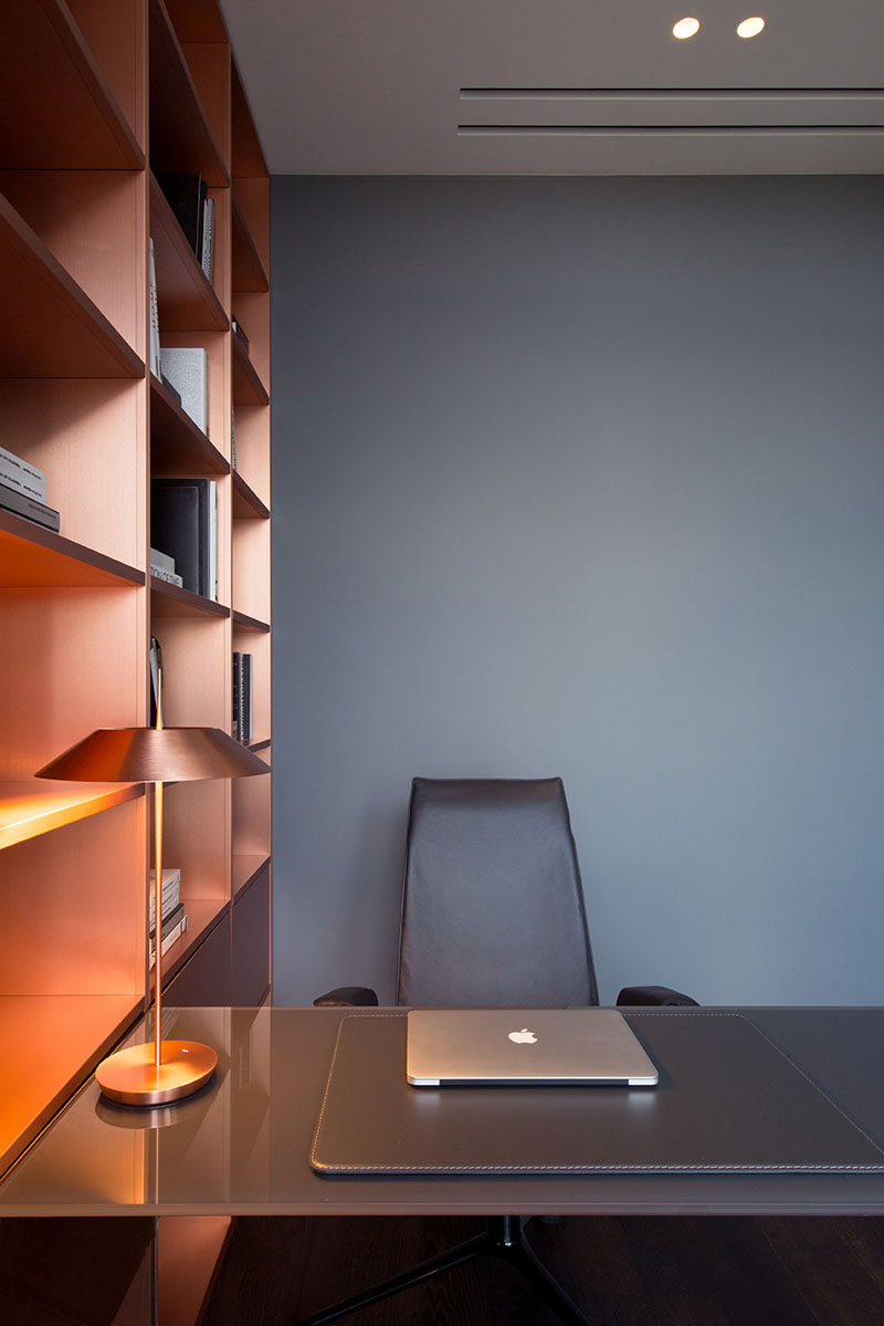 In this modern home office, copper shelving adds a metallic touch to the grey walls. #Copper #GreyWall #HomeOffice